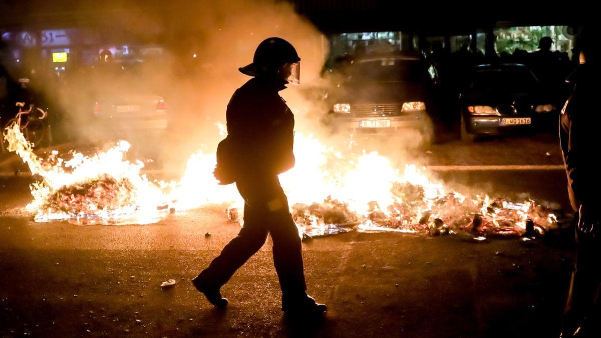 """Ein Polizist geht an einem Feuer auf einer Straße am Rande der Demonstration linker und linksradikaler Gruppen unter dem Motto """"Demonstration zum revolutionären 1. Mai"""" vorbei."""