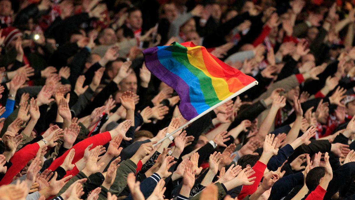 Man sieht Fußballfans des F.C. Bayern, die im vollbesetzen Block eine Regenbogenfahne schwenken.