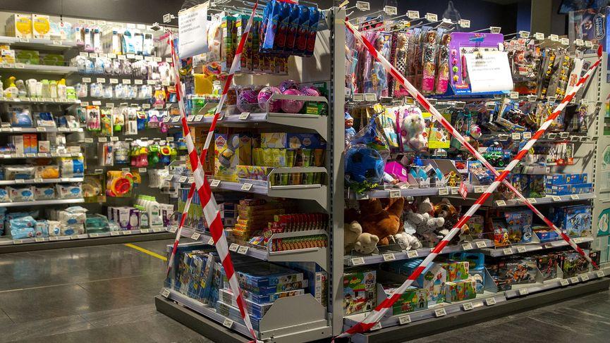 Ein Regal mit Spielzeug, also nicht-essentiellen Waren, ist in einem Supermarkt mit Flatterband abgesperrt