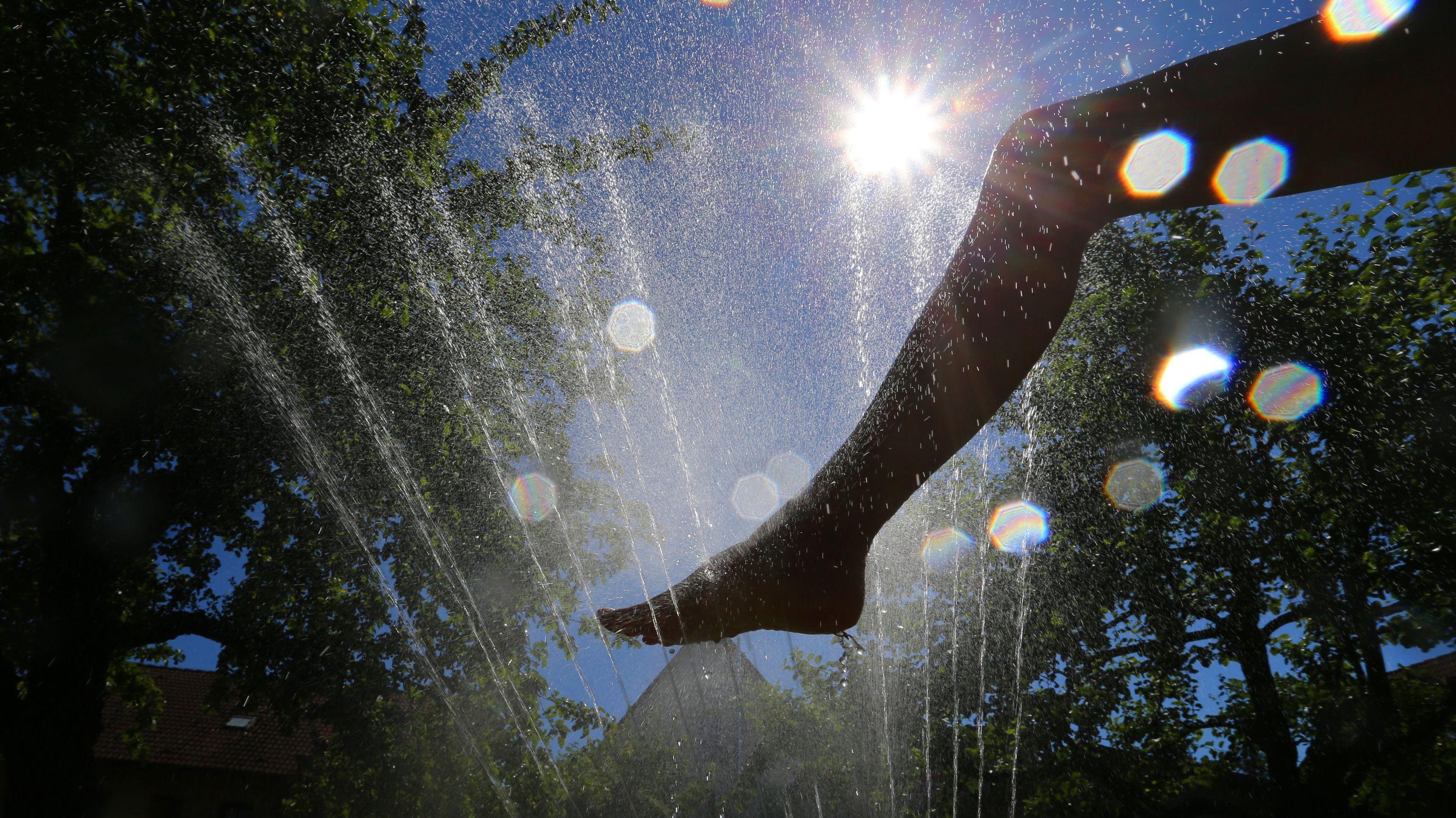 Bayern, Zellingen: Eine Frau kühlt sich in einem Garten unter einem Rasensprenger ab.