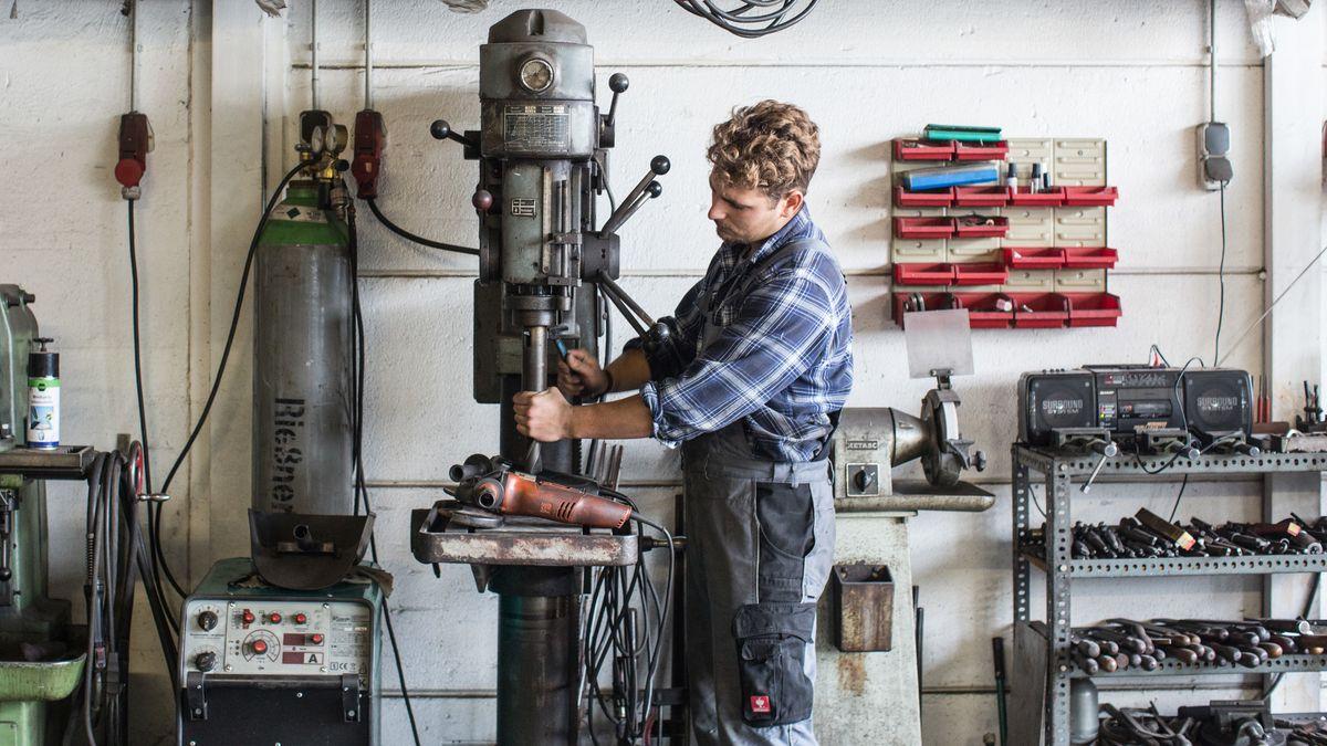 Ein Schlosser steht an einer Ständerbohrmaschine.