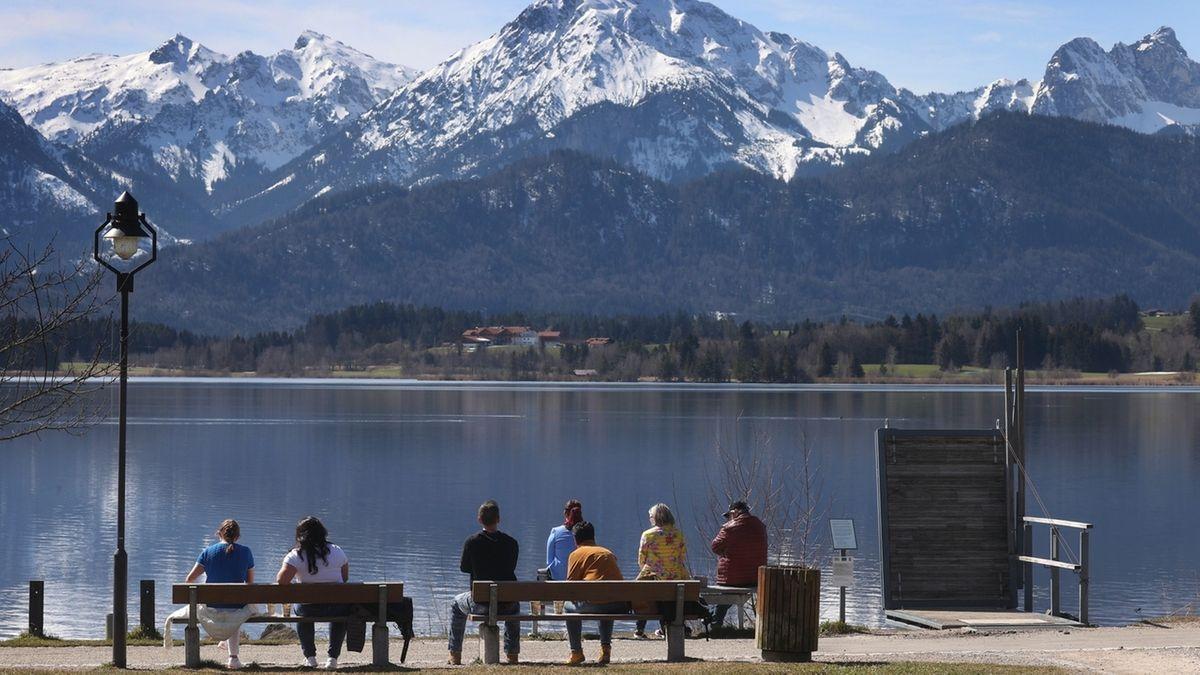 28.03.2021 bei Füssen: Ausflügler sitzen am Ufer des Hopfensees mit Abstand zueinander auf Bänken im Sonnenschein.