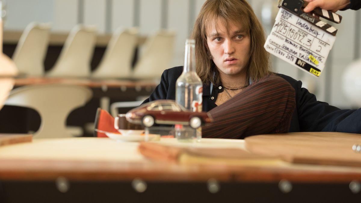 Aufnahme vom Film-Set: Jan Bülow sitzt als Udo lässig vor einem Tisch