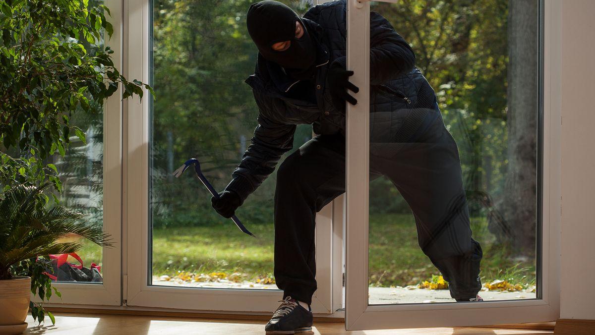 Ein Einbrecher steigt durch die Terrassentür ein (Symbolbild).