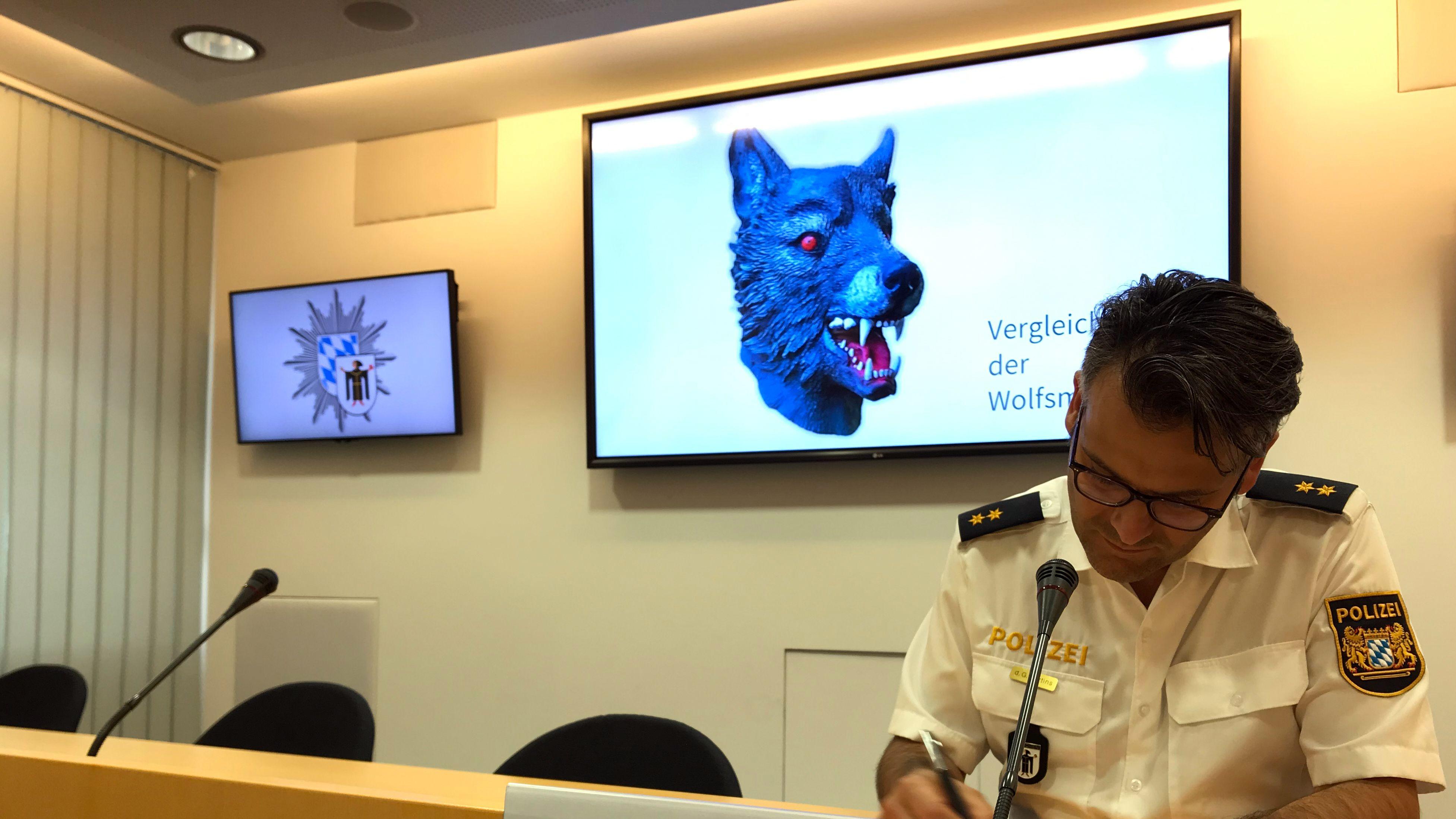 Marcus da Gloria Martins, Sprecher der Münchner Polizei, sitzt vor einem Vergleichsbild einer Wolfsmaske (gestellte Szene).