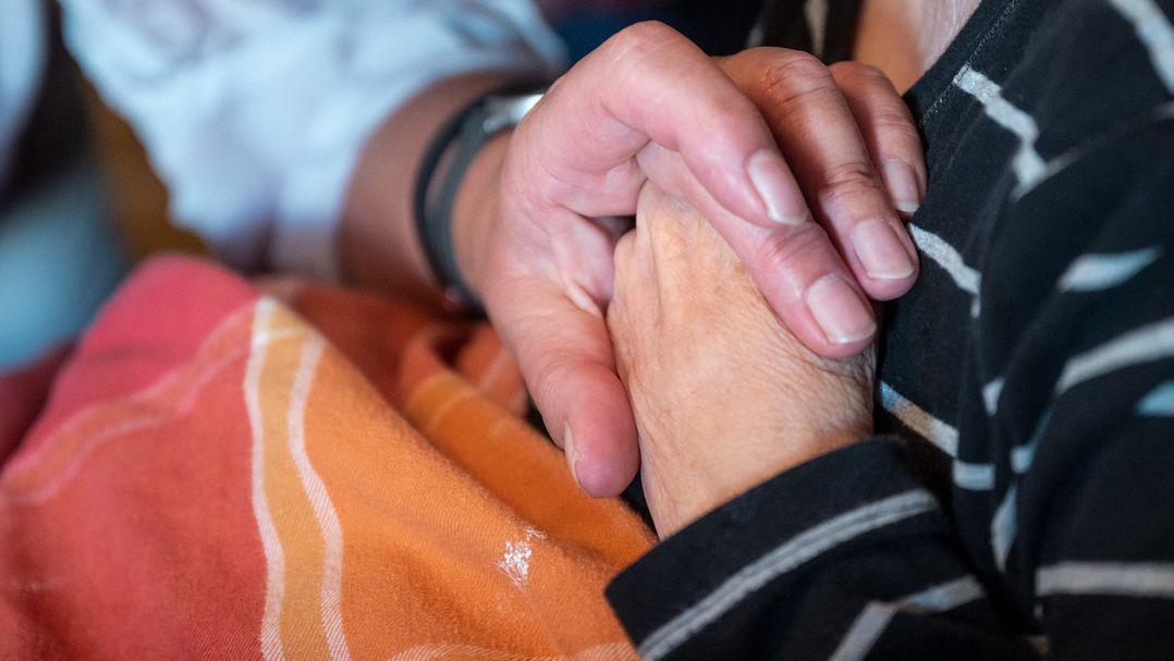 Angehöriger hält Hand einer Dementen