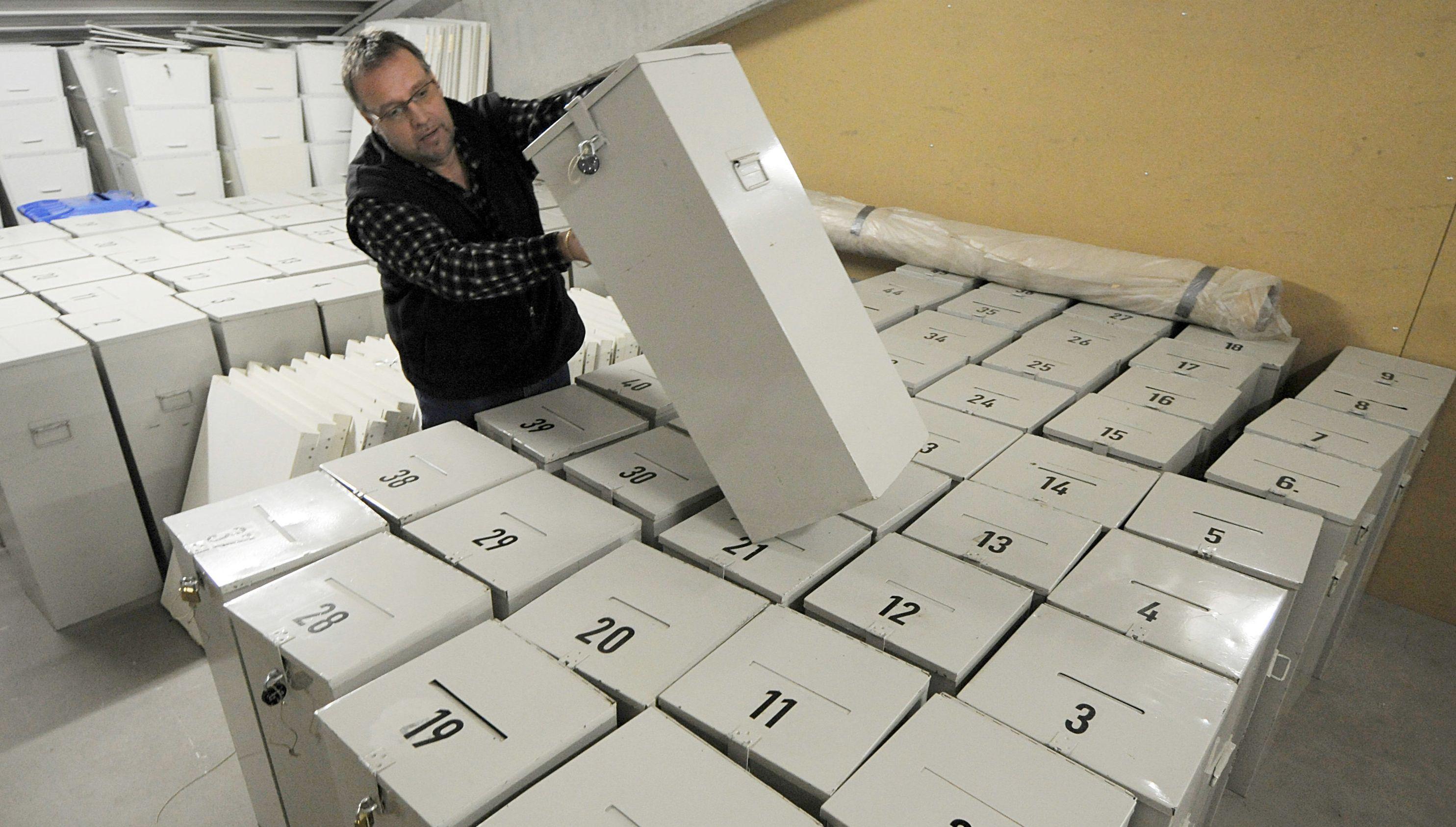 Ein Mann trägt in einem Lager eine Wahlurne