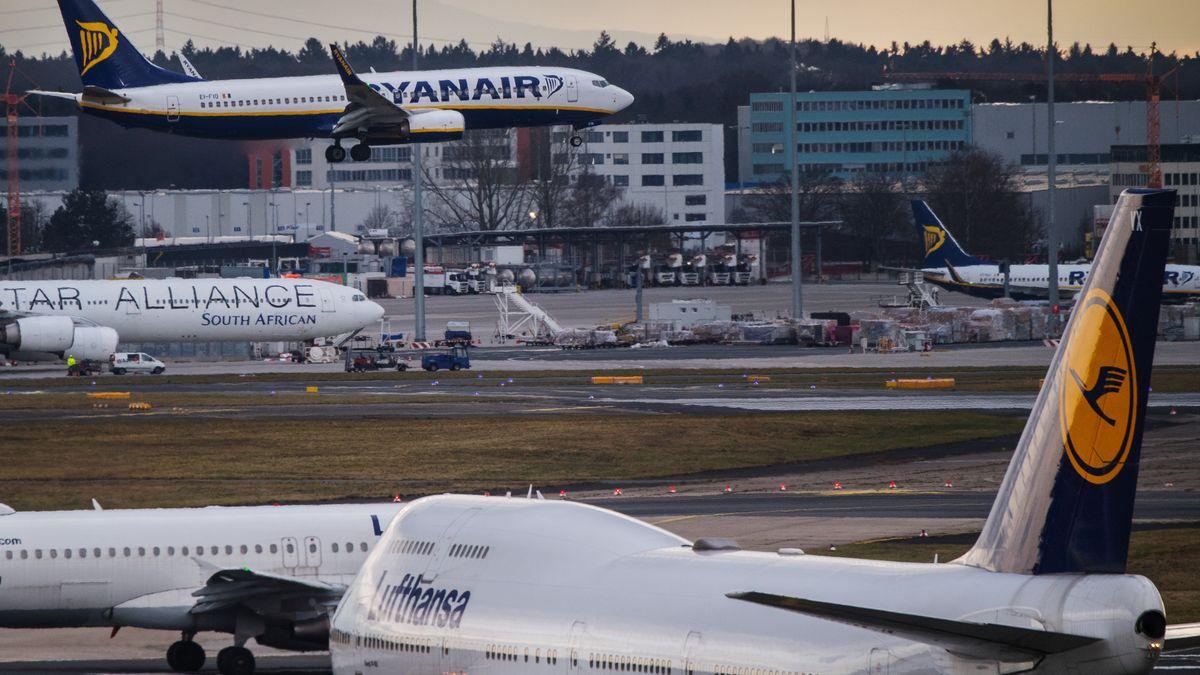 Ein Maschine der Fluglinie Ryanair fliegt im Landeanflug auf den Flughafen in Frankfurt am Main an einer Lufthansa-Maschine vorbei.