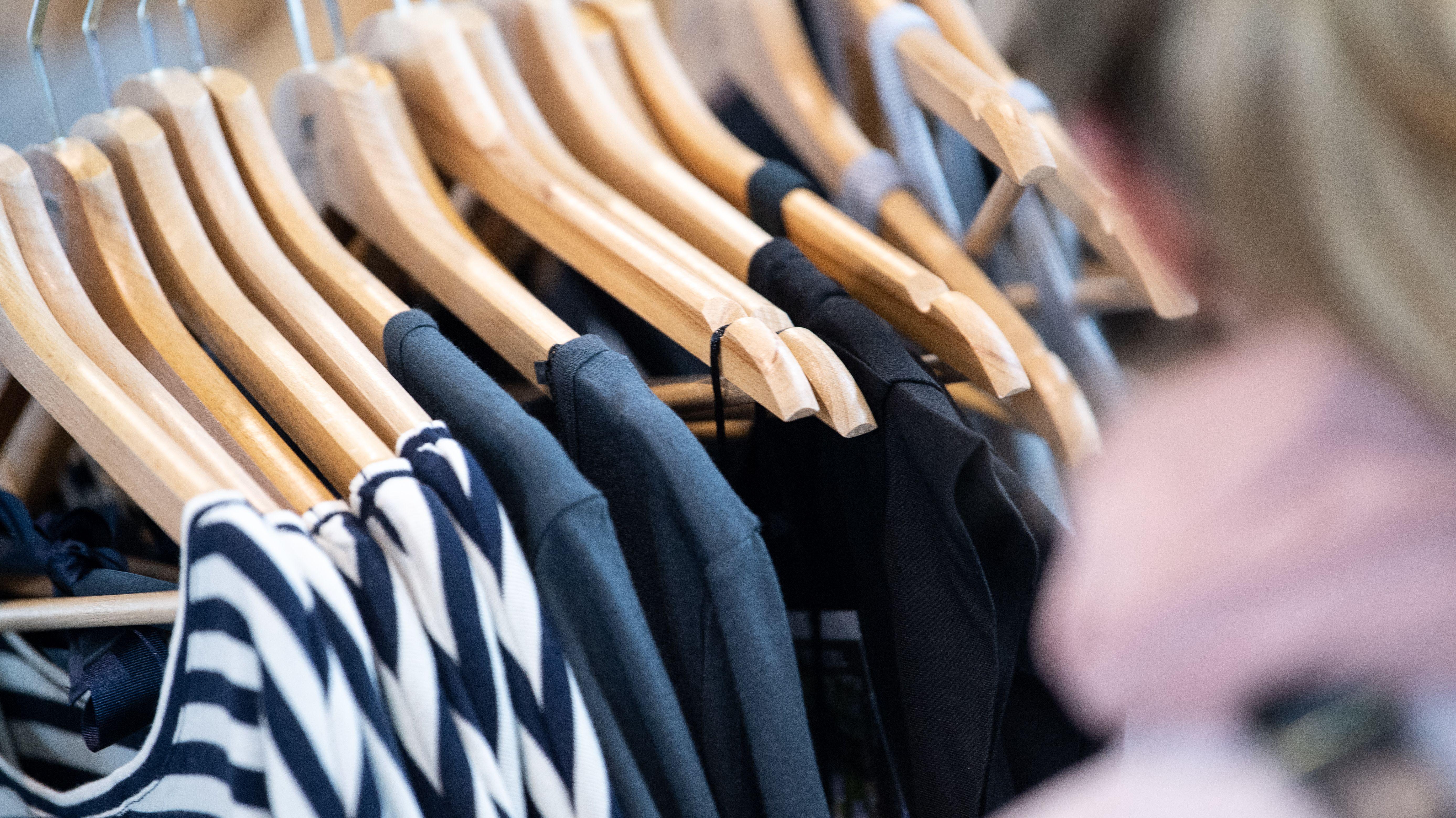Oberteile auf hölzernen Kleiderbügeln: der Trend geht zu nachhaltig produzierter Mode.