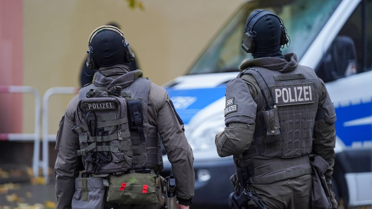 SEK-Polizisten stehen vor einem Polizeiwagen