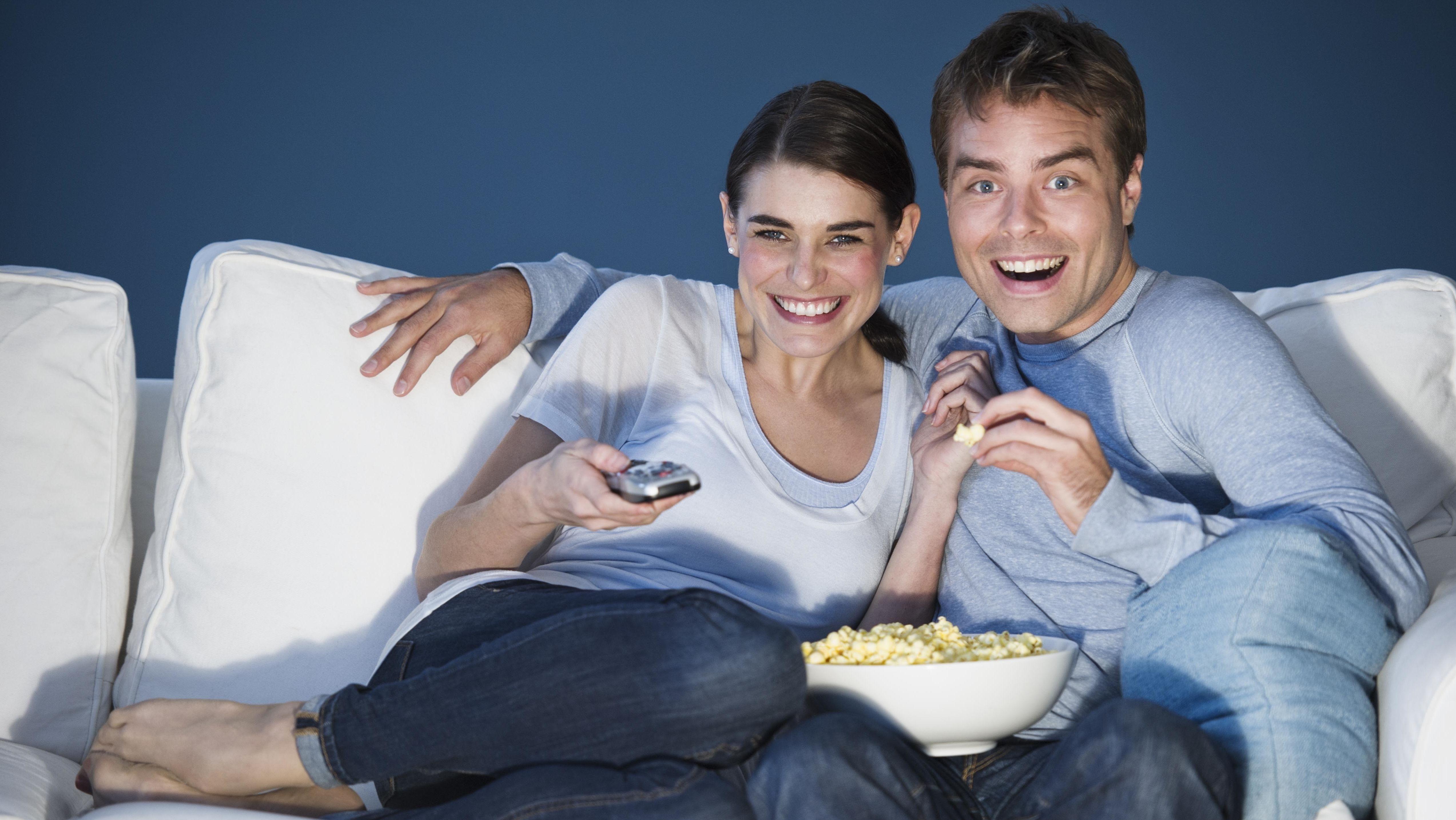 Paar lachend vor dem Fernseher mit Popcorn.
