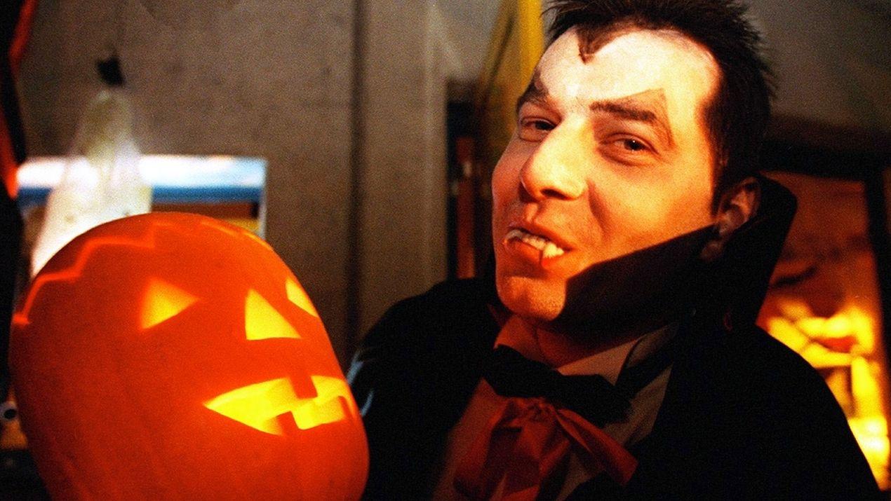 Mann in Halloween-Party-Verkleidung und einem Kürbis in den Händen