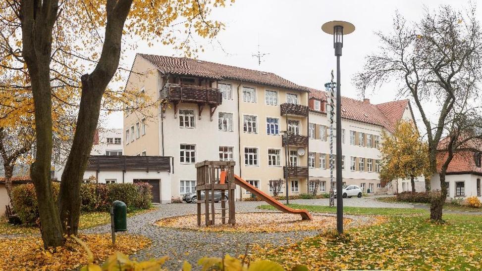 Gebäude des Kinder- und Jugendhilfezentrums St. Josef in Wunsiedel, davor ein Garten und eine Rutsche für Kinder.