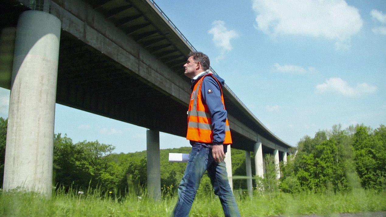 Ein Mann mit oranger Warnweste steht vor einer Brücke.