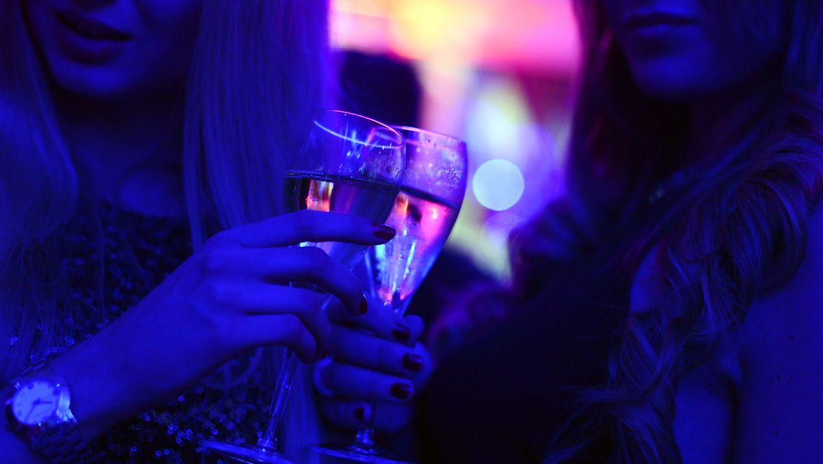 Feiernde stoßen mit Gläsern an