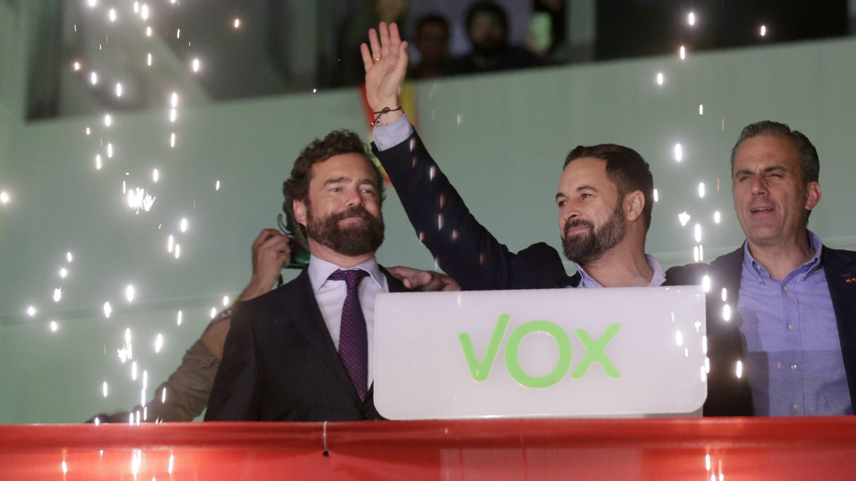 Santiago Abascal (M), Parteivorsitzender der rechtsextremen Vox-Partei, winkt nach der Bekanntgabe der ersten Wahlergebnisse Anhängern vor dem Parteizentrum zu. Rechts und links neben im sind Funken eines Feuerwerks