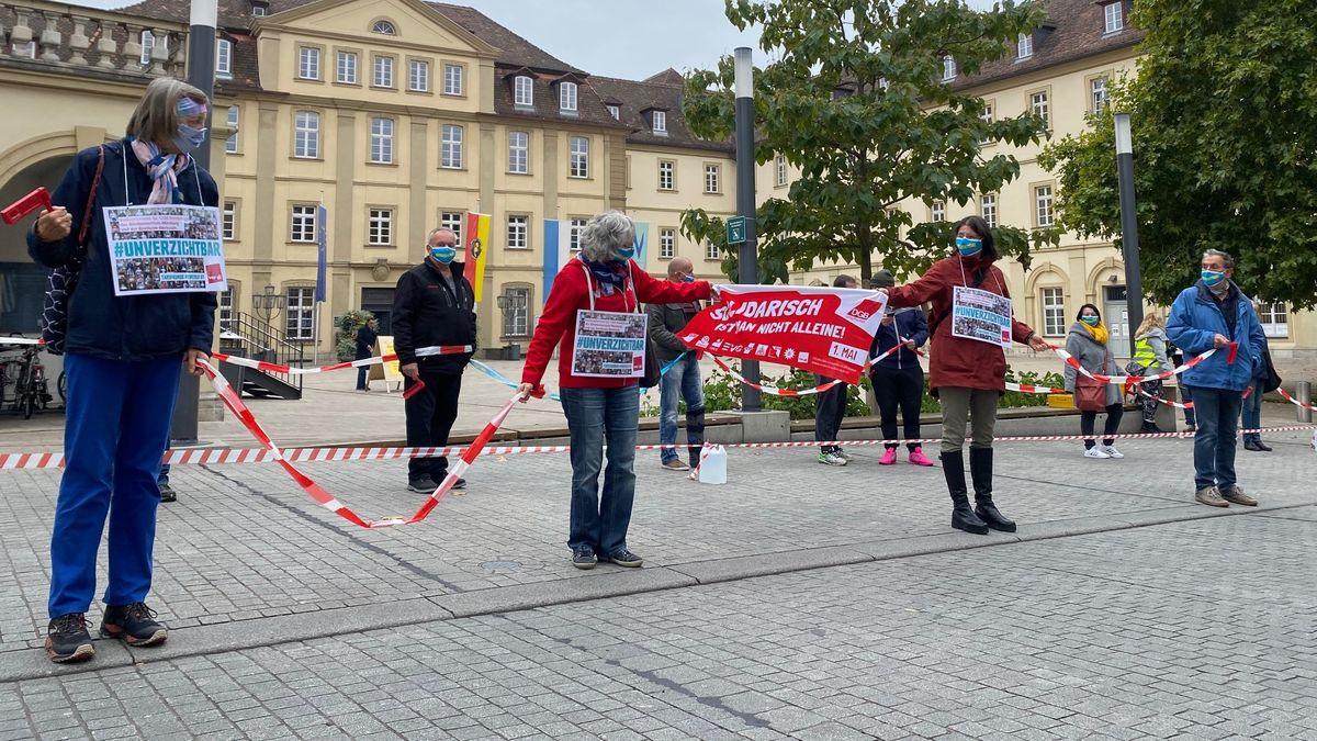 Eine Menschenkette mit Plakaten in der Hand steht vor dem Rathaus.