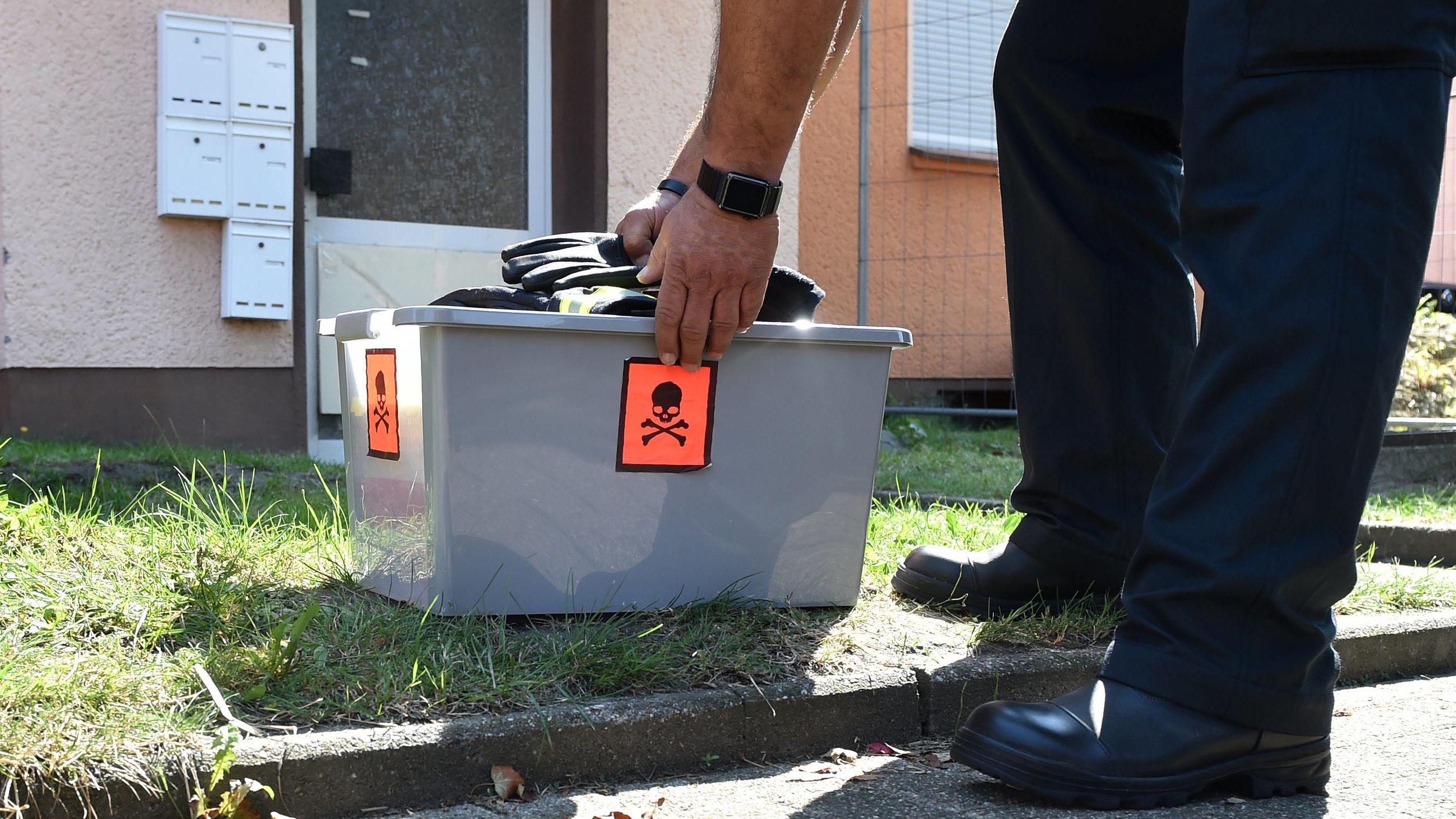 Ein Schlangenexperte stellt eine Kiste vor die Haustür eines Mehrfamilienhauses in Herne. Am Sonntag ist dort eine giftige Kobra entwischt.