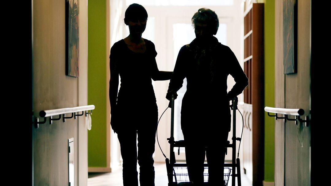 Eine Pflegekraft begleitet die Bewohnerin eines Altenheims mit Rollator beim Gang durch den Flur.