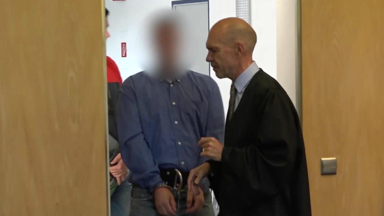 Der Angeklagte betritt in Handschellen den Gerichtssaal