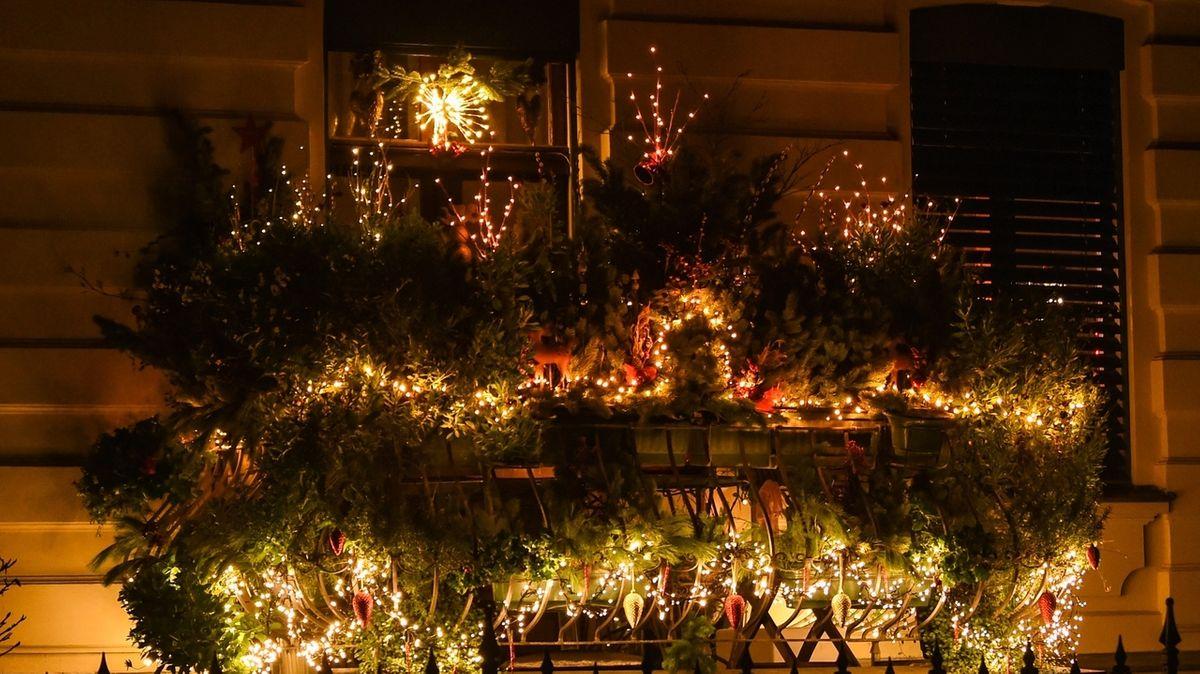 Der Balkon eines Wohnhauses, verziehrt mit Nadelbaum-Zweigen, vielen Lichtern und Weihnachtsschmuck.