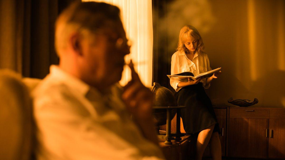 """Im Vordergrund sitzt in gelblichem Licht ein rauchender Mann, vor dem Fenster sitzt eine junge Frau in ein Buch vertieft. Szene aus """"""""Die Tochter des Spions"""""""