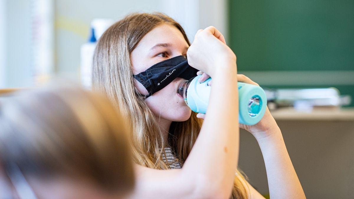 Kind schiebt die Maske hoch im Klassenzimmer, um was zu trinken.