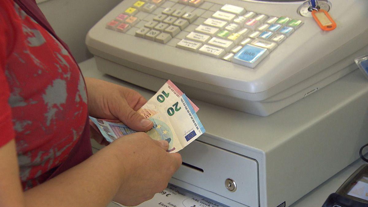 Eine Frau zählt Geldscheine vor einer Kasse