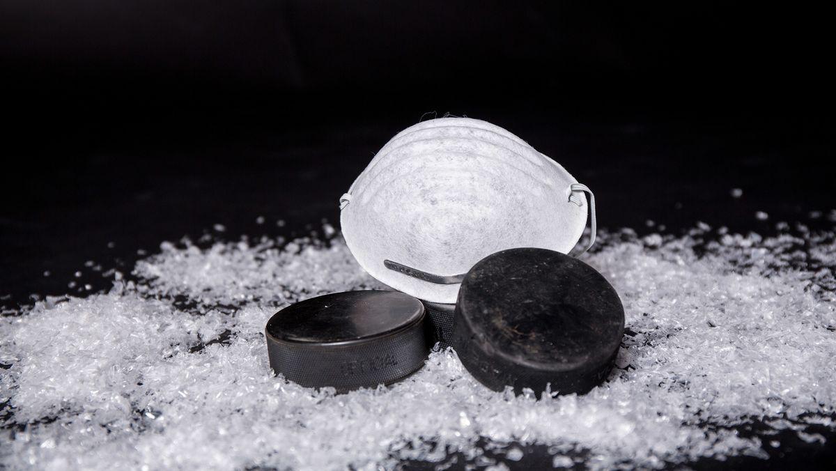 Mundschutz-Maske und Eishockey-Pucks