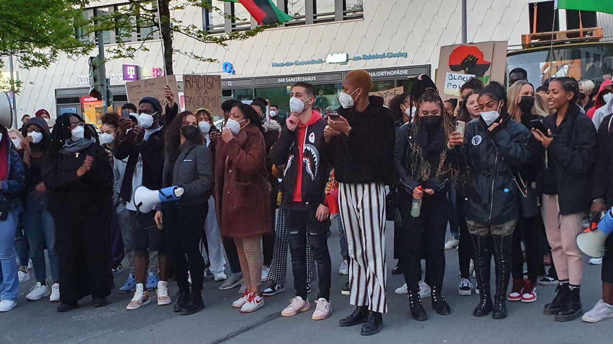 Eine Gruppe überwiegend junger Menschen, die meisten von ihnen People of Color, Masken auf dem Giesinger Bahnhofsplatz; einige von ihnen halten Plakate hoch.