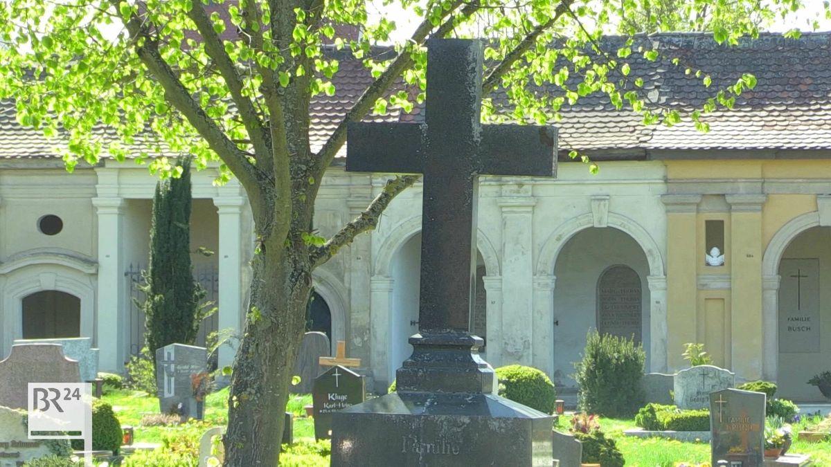 Ein Steinkreuz auf dem Ansbacher Friedhof, umgeben von Gräbern, dahinter die Aussegnungshalle