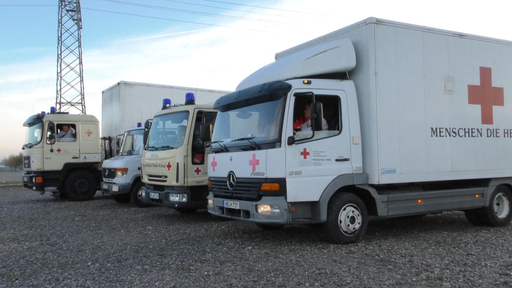 Vier Lastwagen des BRK, die Hilfsgüter geladen haben.