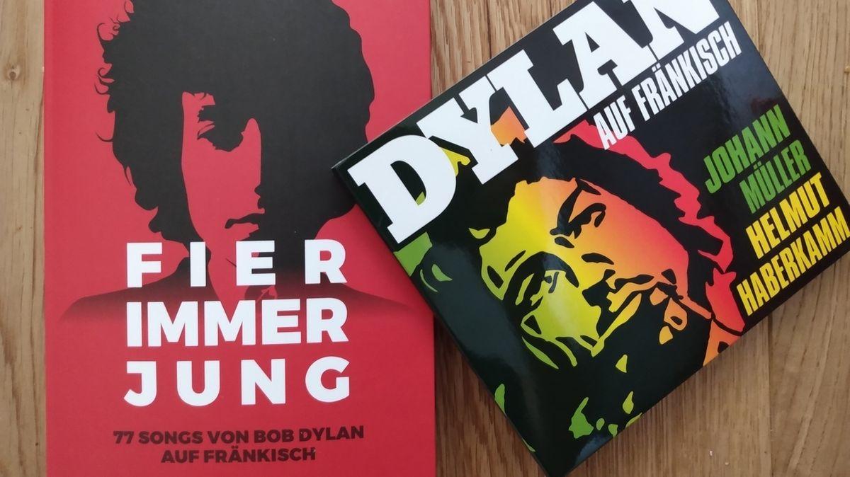 """Rotes Buch mit Bild des jungen Bob Dylan mit dem Titel """"Fier immer jung. 77 Songs von Bob Dylan auf Fränkisch"""", daneben die CD """"Dylan auf Fränkisch""""."""