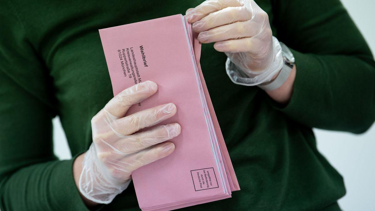 Wahlhelfer mit Schutzhandschuhen und Briefwahlunterlagen