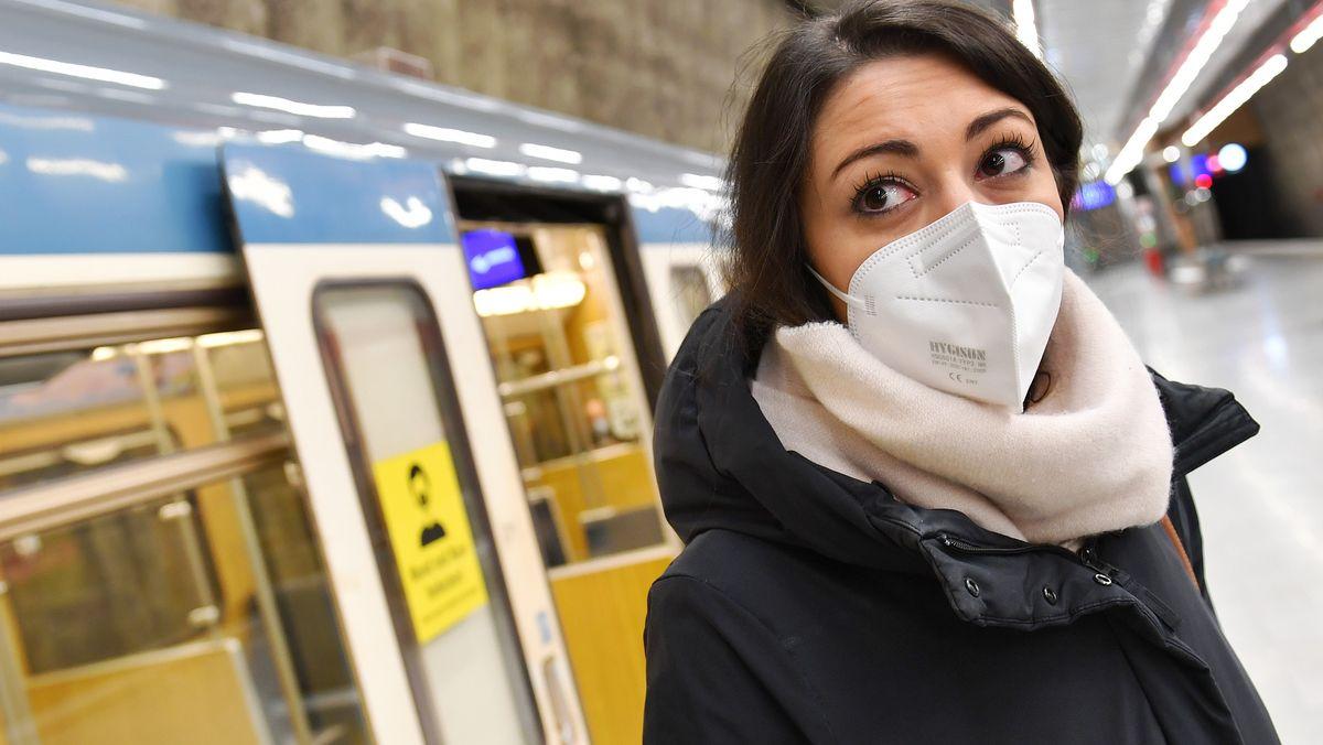 Eine junge Frau mit FFP2-Maske steht vor einem U-Bahn-Waggon in München.