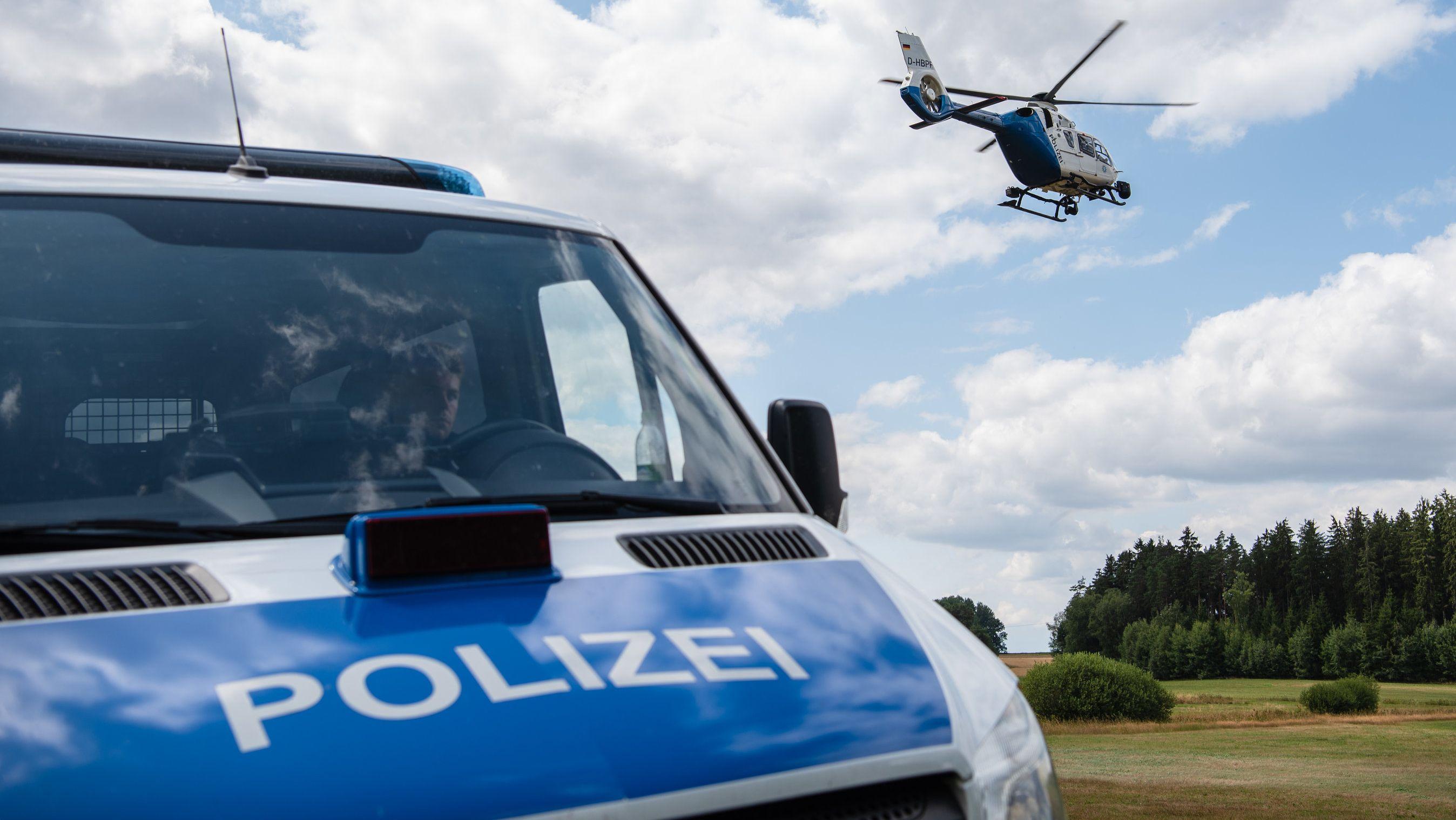 Polizeifahrzeug vor abhebendem Polizeihubschrauber