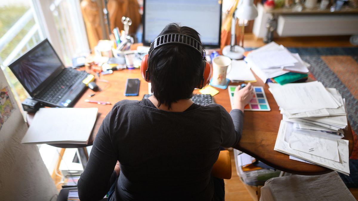 Eine Frau arbeitet mit Hörschutz im Homeoffice