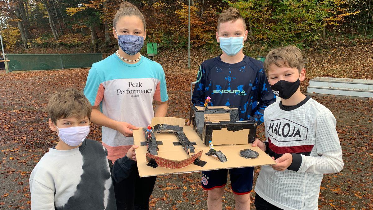 Vier Jugendliche zeigen ein 3D Modell ihres Wunsch-Bike-Parks aus Pappe.