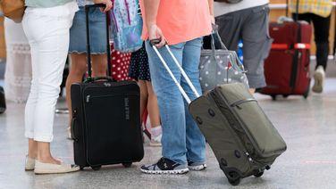 Menschen mit Koffern warten an einem Flughafen auf ihren Flug. | picture alliance/dpa | Peter Steffen