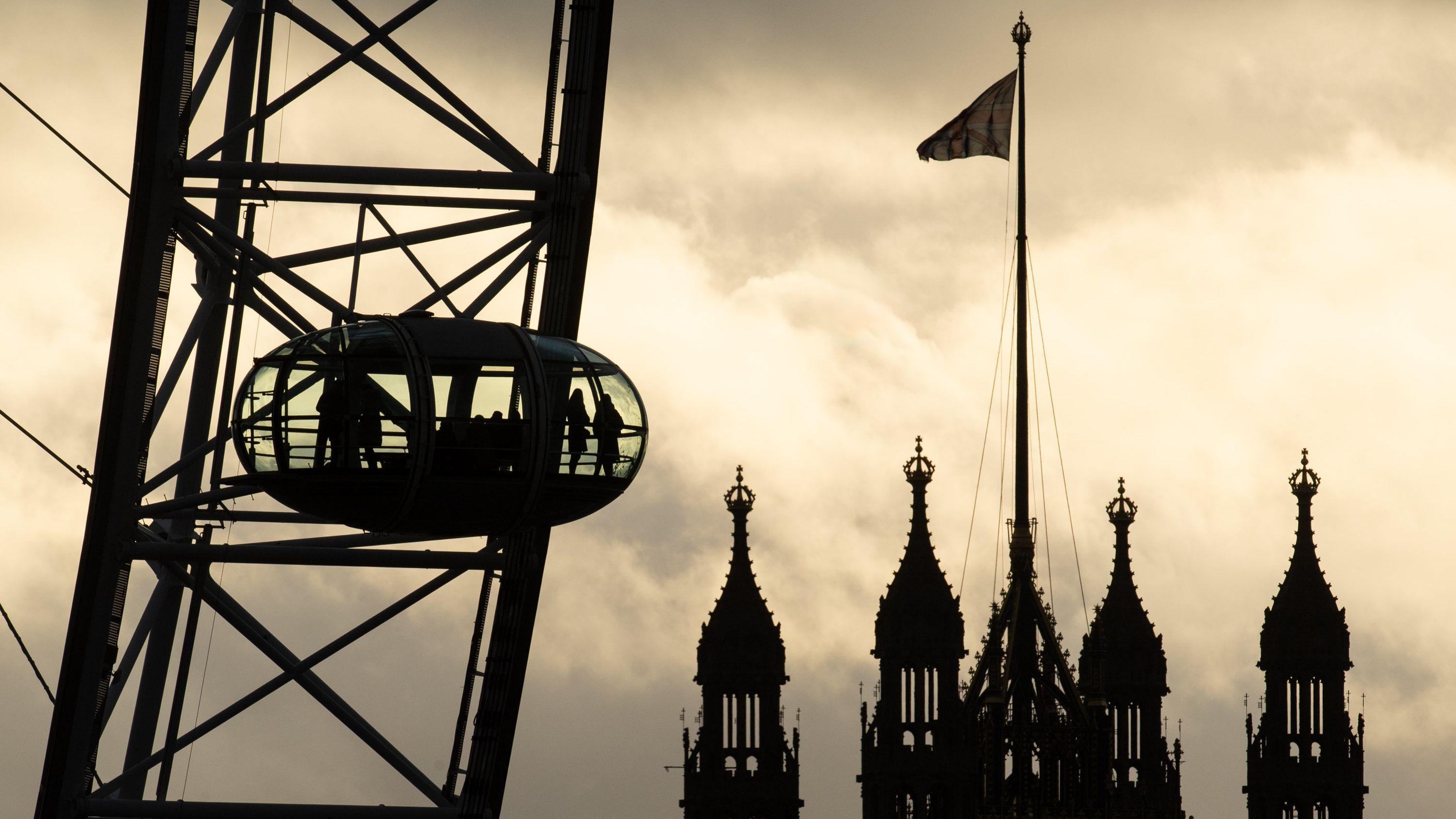 Touristen sitzen in einer Gondel des London Eye, während im Hintergrund das britische Parlament zu sehen ist.