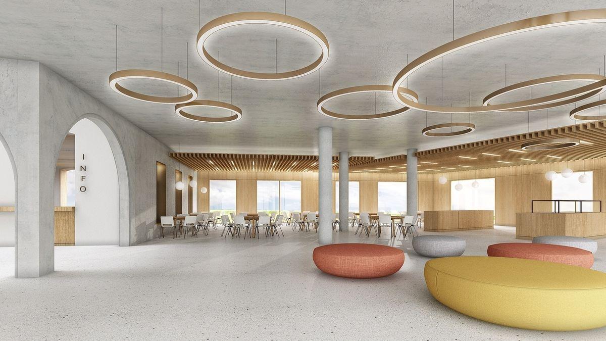 Ein großer Raum, von dessen Betondecke runde Lichtkreise hängen, darunter stehen runde gelbe und rote Sitzpolster.