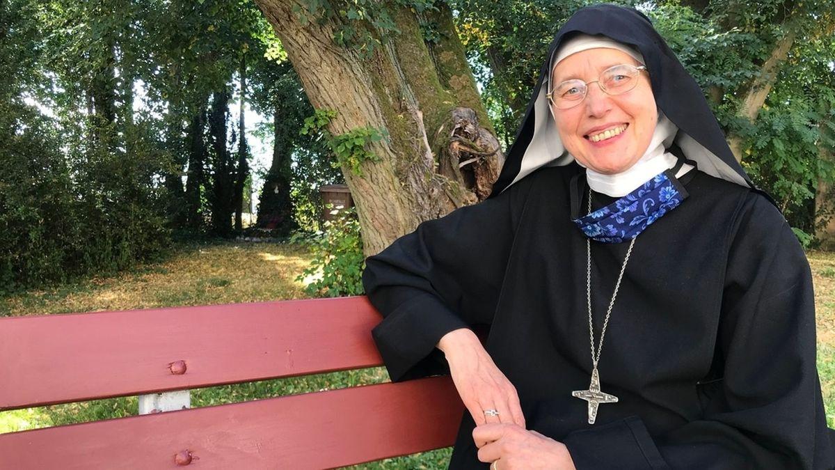 Äbtissin Mechthild Thürmer im schwarzen Ordenhabit sitzt auf eine roten Bank.