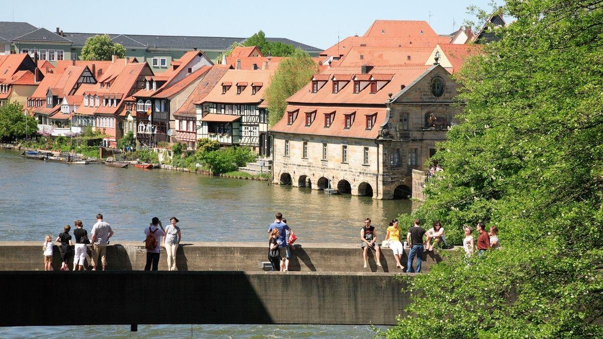 Blick über die Untere Brücke auf die Regnitz mit dem historischen Schlachthaus in Bamberg