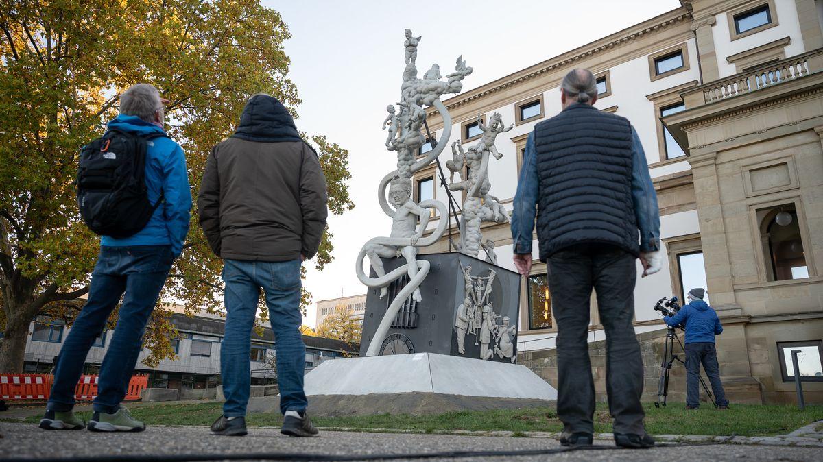 Drei Passanten vor der Skulptur