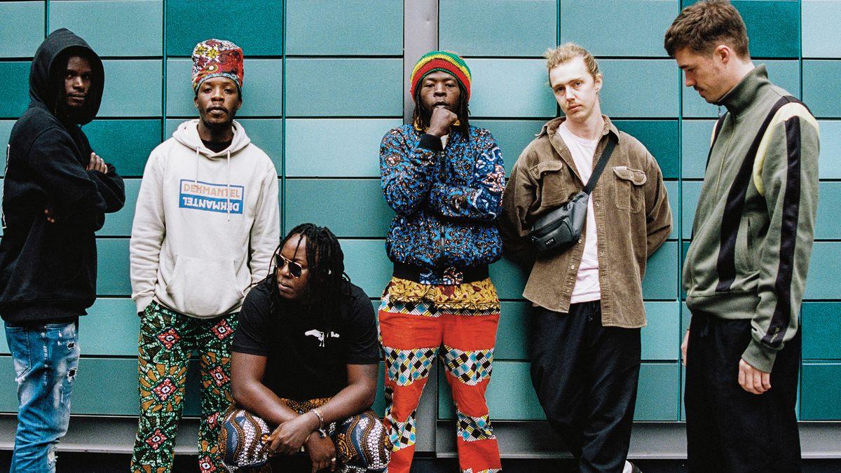 Vier schwarze und zwei weiße junge Männer stehen vor einer türkisen Wand: die ugandisch-britische Band Nihiloxica