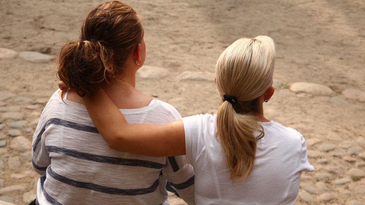 Zwei lesbische Frauen sitzen Arm in Arm auf einer Parkbank