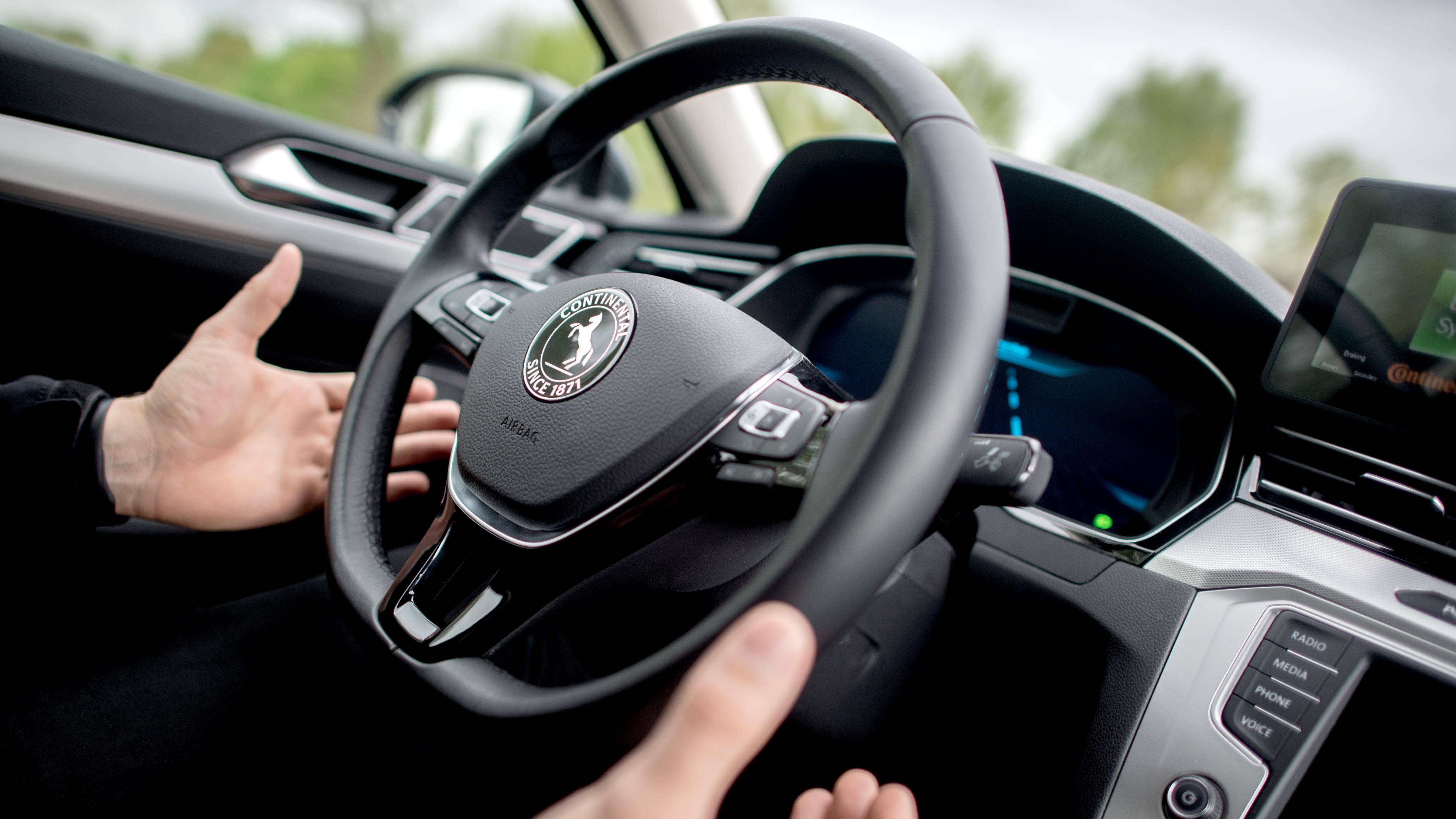 Mann in autonomem Fahrzeug nimmt Hände vom Lenkrad