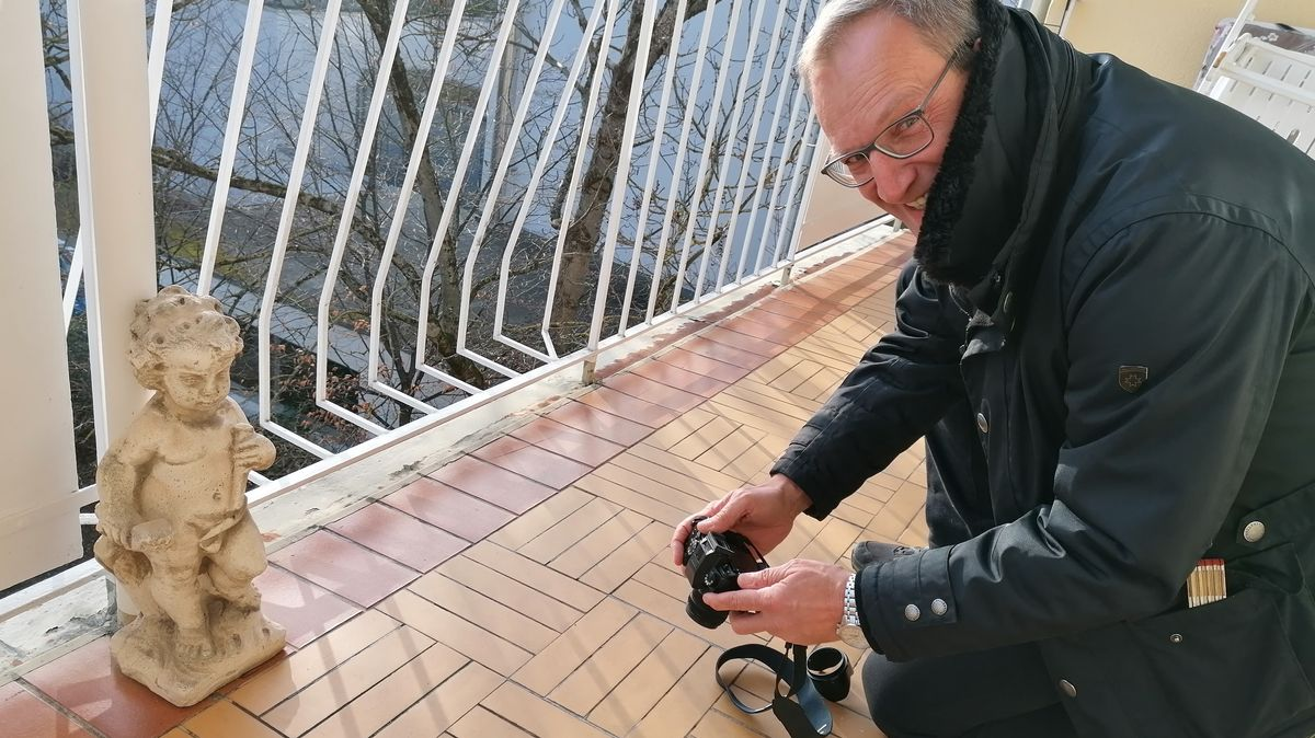 Mann mit Kamera auf Balkon