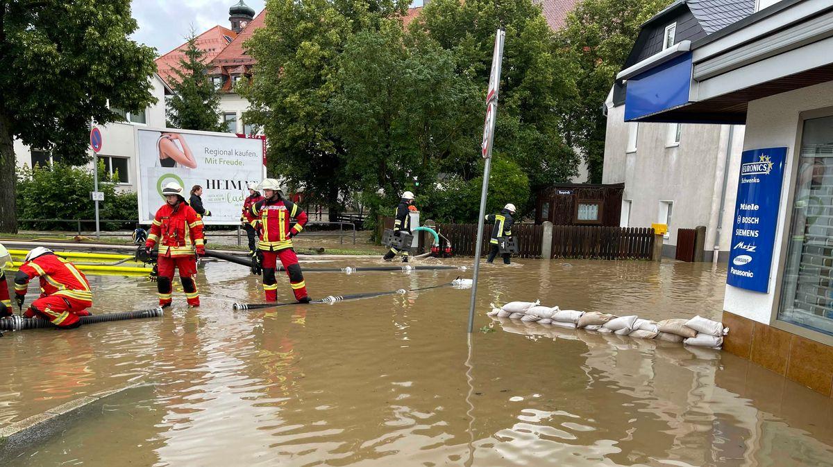 Einsatzkräfte stehen auf einer überschwemmten Kreuzung in Selbitz im Landkreis Hof.