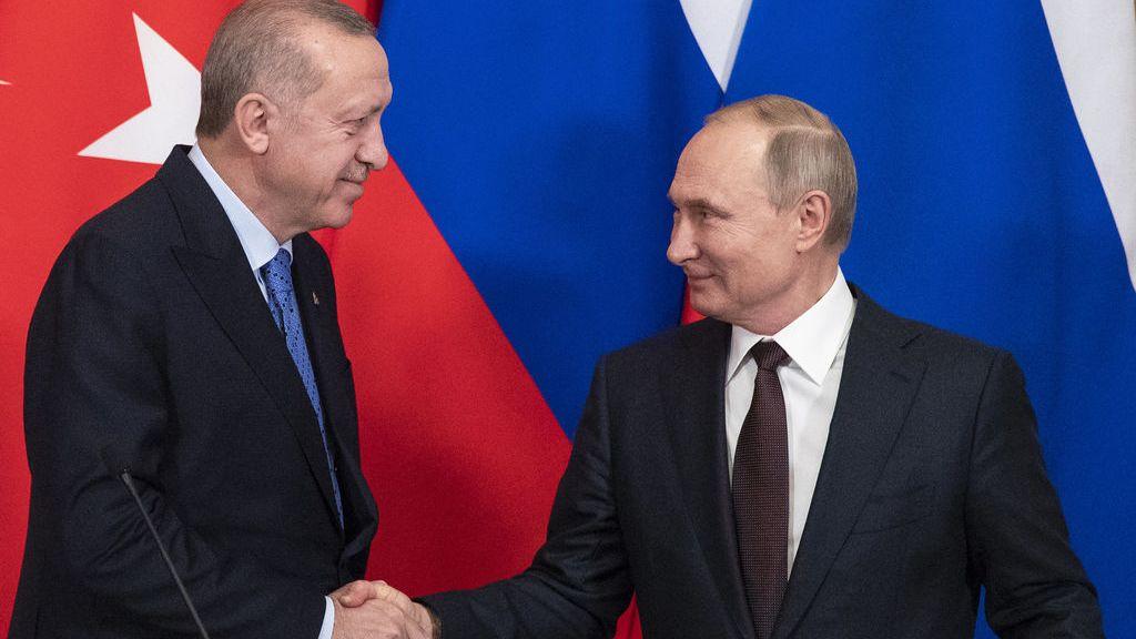 Der russische Präsident Wladimir Putin (r) und der türkische Präsident Recep Tayyip Erdogan reichen sich nach ihren Gesprächen im Kreml bei einer Pressekonferenz die Hände. Die Türkei und Russland haben sich auf eine neue Waffenruhe in der syrischen Rebellenhochburg Idlib geeinigt.